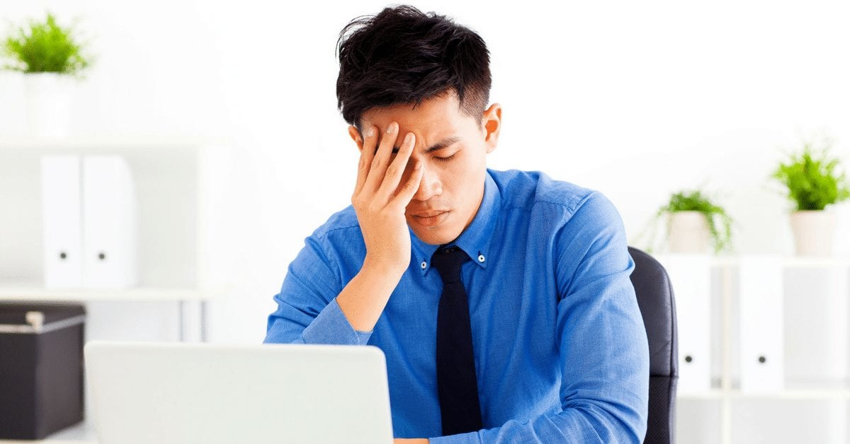 Man holding head related to caffeine and migraine