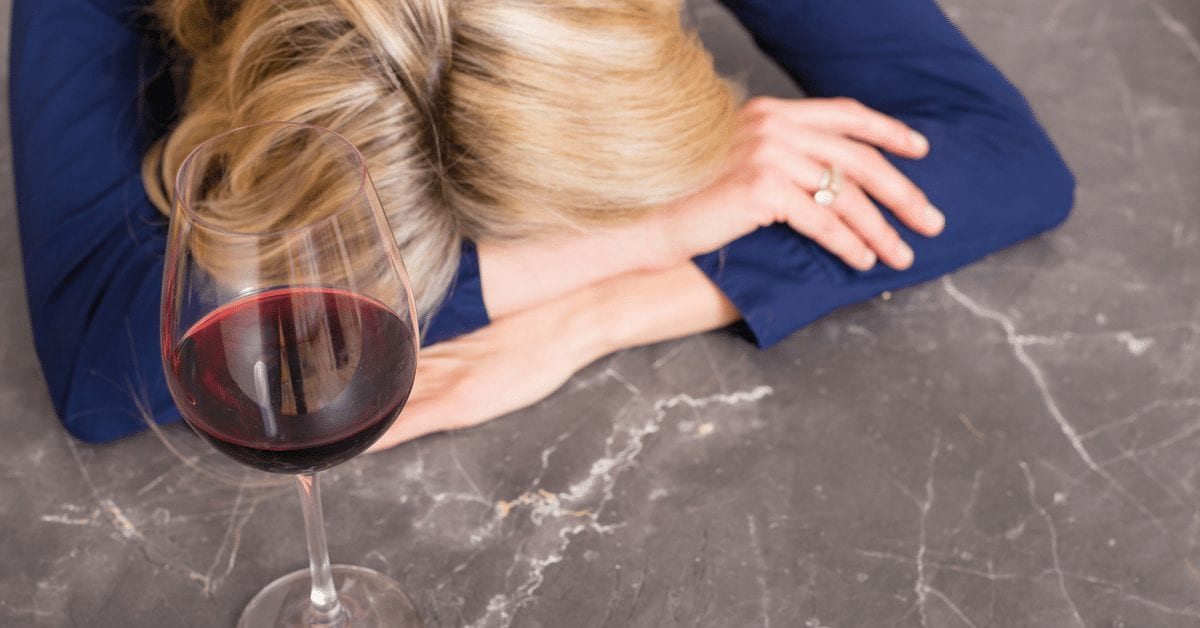 woman resting head with wine - effect of alcohol and migraine