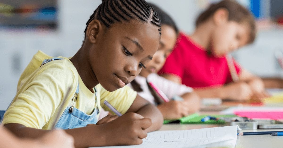children in classroom writing in notebooks